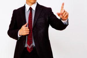 人差し指を立てるスーツの男性